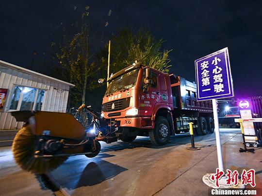 乌鲁木齐夜色中进行冬季城市道路积雪清运应急演练