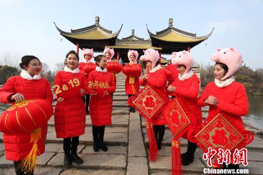 图为瘦西湖风景区导游头戴卡通猪帽,手拿中国结和红灯笼,在五亭桥上